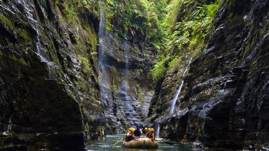 raft makes its way through a narrow canyon on the Upper Navua River in Fiji
