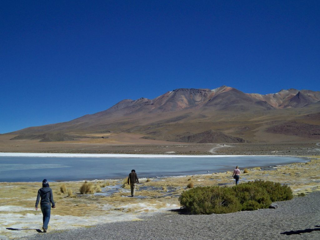 Walking alongside colored lakes with fellow travelers at Bolivia's Salar de Uyuni. ©Sabine Bergmann