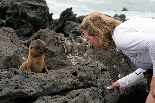 tourist with baby seal in the Galapagos